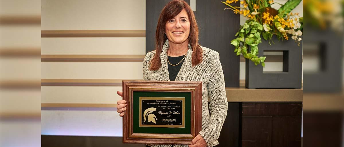 Betsy Meter holds her framed award