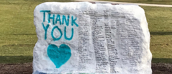 The Rock, painted white, with 'THANK YOU' and a heart painted on in teal, and next to it black lettering of all the survivors who testified at Larry Nassar's Ingham County sentencing.