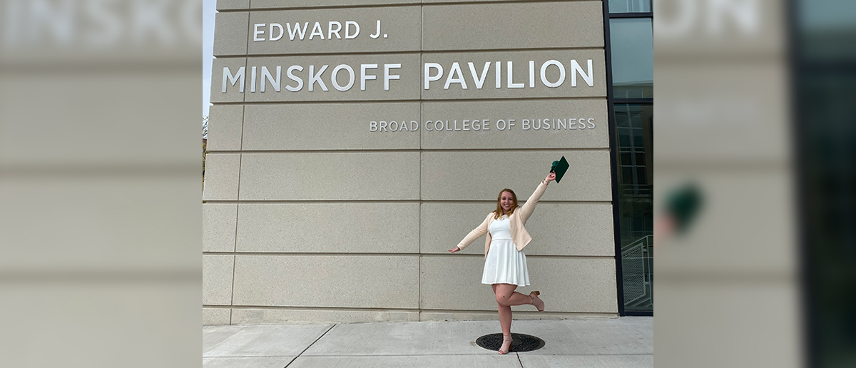 Broad graduating senior Alexa Avendt poses with her graduation cap in front of the Minskoff Pavilion's main entrance sign on campus.