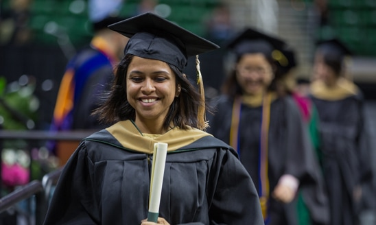 Female Broad College graduate student crosses the commencement stage with her diploma in-hand.