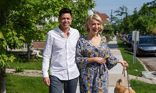 Hospitality business alumni Kyle Welch and Alex Clark walk down a sidewalk on a sunny day.