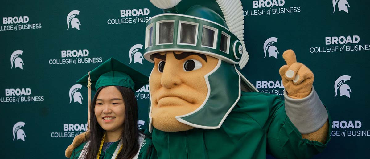 A Broad College student takes a picture with the mascot Sparty in front of Broad College of Business backdrop