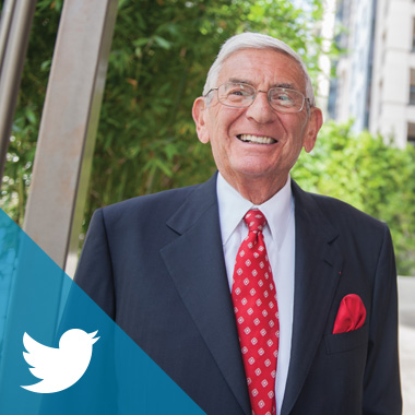 Eli Broad in a navy suit and red tie stands outside on a sunny day