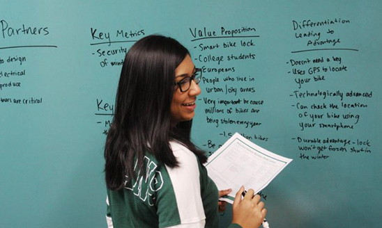 A student smiles and takes notes on a blue board with a dry erase marker.