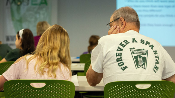 A granddaughter sits in class with her grandfather, who is wearing a 'Forever a Spartan - Grandparents University' T-shirt