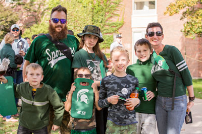 A family dressed in Spartan apparel at Homecoming