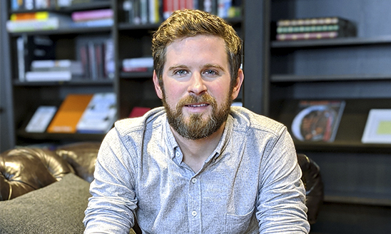MSU alumnus and creative director at Google Creative Lab Jesse Juriga sits in a leather chair in an office with a bookshelf in the background.