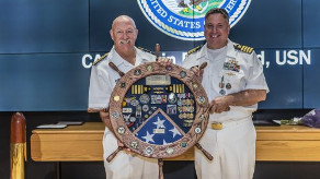 Justin Debord (right) poses with ship's wheel shadow box presented to him at his Navy retirement. Photo courtesy of Justin Debord.