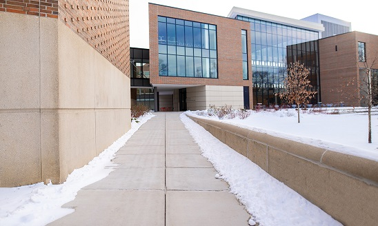 View of the MSU Broad College of Business Edward J. Minskoff Pavilion from a sidewalk leading up to the building