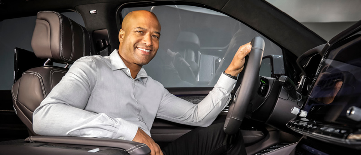 Alumnus and global president of product design at Fiat Chrysler Automobiles Ralph GIlles sits in the driver seat of a car he's designed.