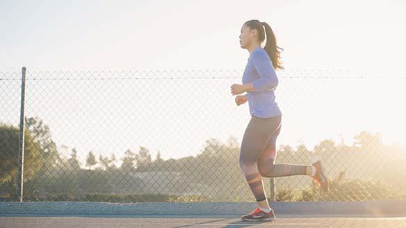 A woman runs on the sidewalk as the sun rises.