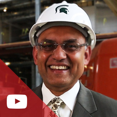 Dean Sanjay Gupta poses with a hard hat on inside the Pavilion under construction