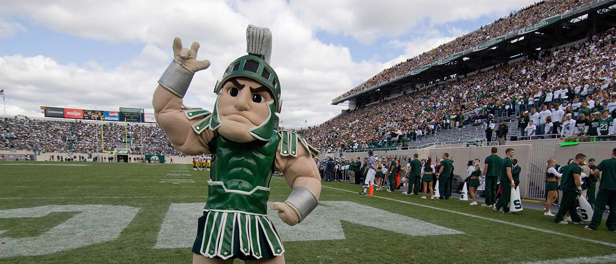 "Sparty stands on the football field and signs ""I love you"" in American Sign Language."