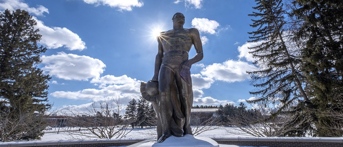The Sparty statue on MSU's campus picture on a vibrant sunny day in winter.
