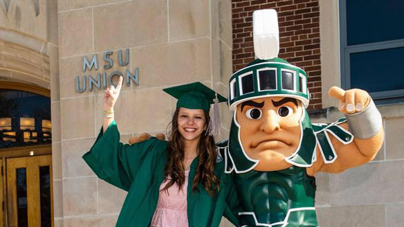 Nicole Niemiec, one of the Sparty mascot wearers, poses in front of the MSU Union in her graduation regalia with Sparty