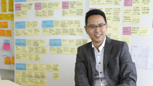 Stephen Wong, pictured in front of a background of colorful sticky notes