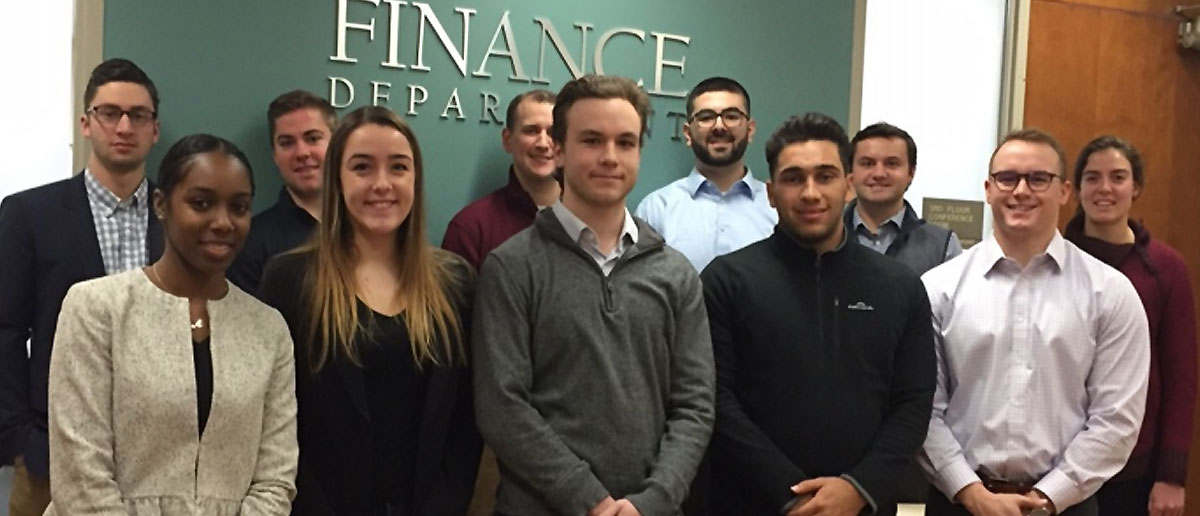 Student venture capitalists stand next to each other and pose for a picture in front of the Finance Department sign