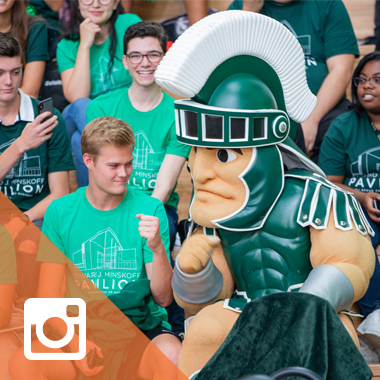 A student fist-bumping with Sparty at the Minskoff Pavilion ribbon cutting event.