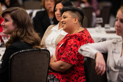 A woman smiles and engages with others at the Broad College's annual Advancing Women in Busine