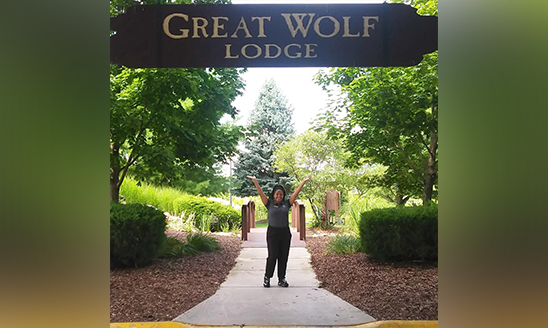 Hospitality student Foressia Hood stands under the Great Wolf Lodge sign.