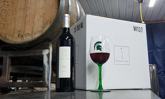 A look inside Hickory Creek Winery, showing a barrel, a bottle of wine and a wine glass with a Spartan helmet logo on it.