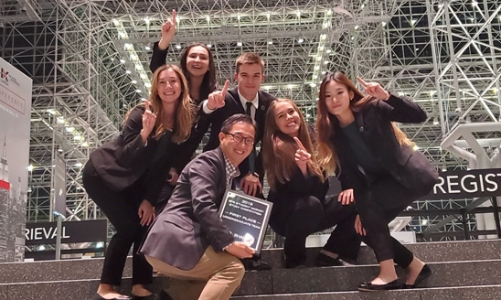 The undergraduate team and associate professor Seung Hyun Kim celebrate the team's first-place award.