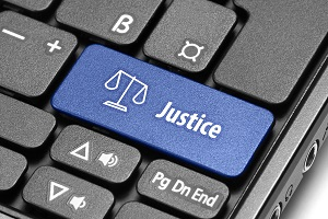 IMAGE: A computer keyboard. The word Justice is spelt out in white letters on a blue key.
