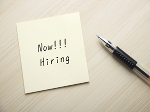 IMAGE: A post-it-note on a table with text on it that says 'Now!!! Hiring'. There is a pen next to the paper