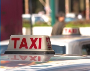 IMAGE: Taxi Cab roof sign. Red block letters spell out Taxi. Image courtesy of Stuart Miles at FreeDigitalPhotos.net